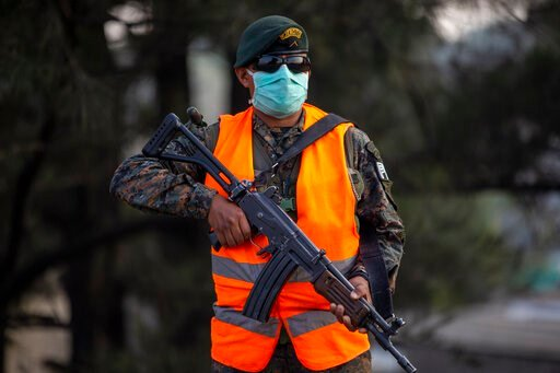 (AP Photo/Moises Castillo). A soldier mans a checkpoint during the fourth day of a curfew to help prevent the spread of the new coronavirus in Villa Nueva, Guatemala, Wednesday, March 25, 2020. COVID-19 disease causes mild or moderate symptoms for most...
