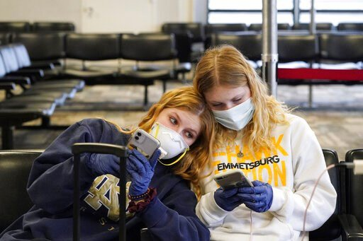 (Anthony Souffle/Star Tribune via AP). Rachel Miner, 15, left, of Emmetsburg, Iowa, sits with Carlotta Haas, 15, a foreign exchange student from Duesseldorf, Germany, who had been living with Miner and her family but was called home, as they waited for...