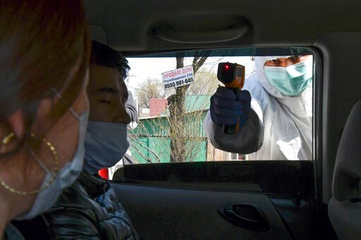 (AP Photo/Vladimir Voronin). In this Wednesday, March 25, 2020, photo, a medical worker checks temperatures of a car passengers at a checkpoint near Bishkek, Kyrgyzstan. For most people, the new coronavirus causes only mild or moderate symptoms. For so...