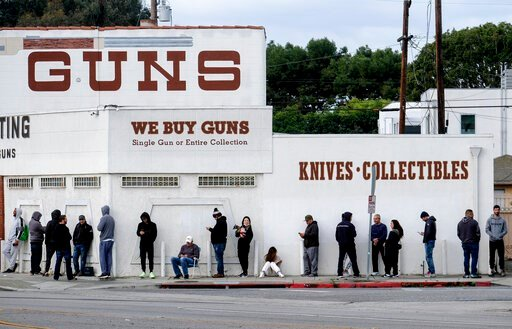 (AP Photo/Ringo H.W. Chiu). People wait in a line to enter a gun store in Culver City, Calif., March 15, 2020.