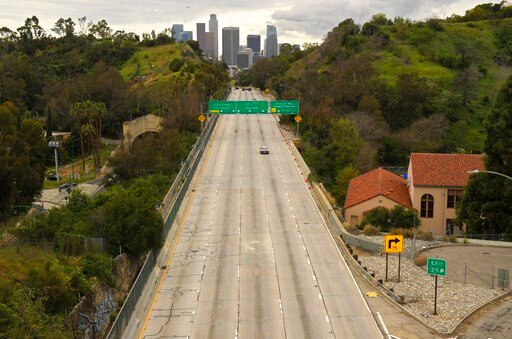 (AP Photo/Mark J. Terrill). FILE - In this March 20, 2020 file photo, extremely light traffic moves along the 110 Harbor Freeway toward downtown mid afternoon, in Los Angeles. For the millions of Americans living under some form of lockdown to curb the...