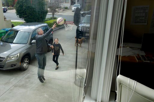 (AP Photo/Jeff Chiu). In this Thursday, March 19, 2020, photo, Frankie Keenan shoots baskets with his daughter Rachel, 9, at their home in San Francisco. California's Bay Area has been shut down for more than a week, the first region of America to orde...