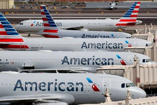 (AP Photo/Matt York, File). FILE - In this Wednesday, March 25, 2020 file photo, American Airlines jets sit idly at their gates as a jet arrives at Sky Harbor International Airport in Phoenix. The Trump administration is raising the possibility of the ...