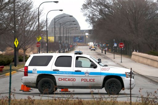 (AP Photo/Charles Rex Arbogast). A Chicago police officer blocks the road to the Adler Planetarium along Lake Michigan Thursday, March 26, 2020, in Chicago. On Thursday morning, Chicago Police began turning joggers and others away from the city's lakef...