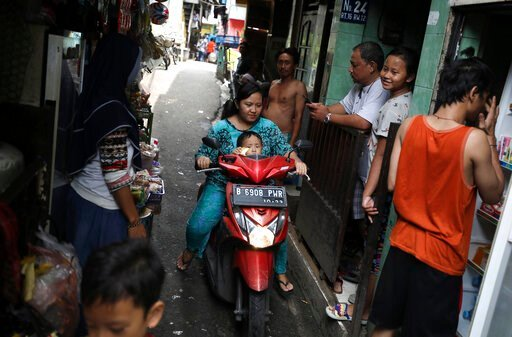 (AP Photo/Dita Alangkara). A motorist rides past as residents talk on an alley at a low-income neighborhood in Jakarta, Indonesia, March 23, 2020.As the virus spreads, the World Health Organization has pointed out that the future of the pandemic will ...