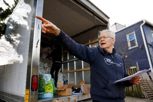 """(AP Photo/Jacquelyn Martin). Mark Andersen, 60, co-director of the nonprofit organization, """"We Are Family DC,"""" organizes groceries and food to be brought to seniors, Saturday, March 21, 2020, in Washington. Seniors are being encouraged to stay in their..."""