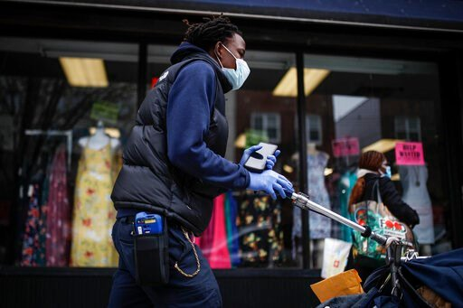 (AP Photo/John Minchillo). FILE - In this Friday, March 20, 2020 file photo, a postal worker wears a protective mask and gloves while operating a route in the Queens borough of New York. Health experts say the risks are very low that coronavirus will r...