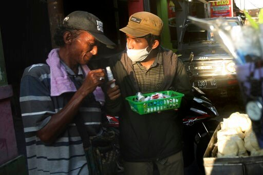 (AP Photo/Fahmi Rosyidi). In this Thursday, March 26, 2020, photo, an activist distribute hand sanitizers and soaps to a street food vendor in Yogyakarta, Indonesia. A group of students from several universities in the central Java city has distributed...