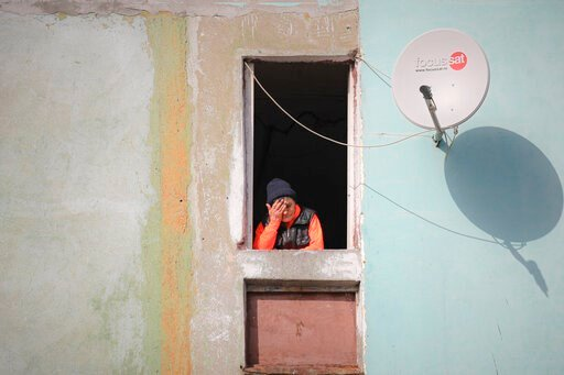 (AP Photo/Vadim Ghirda). An elderly woman stands in a window in a poor area of Bucharest, Romania, Friday, March 27, 2020 as authorities try to limit the spread of the new coronavirus, one of the measures being forbidding people over 65 years of age to...