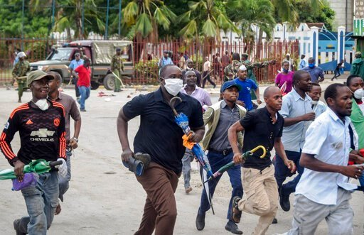 (AP Photo). Ferry passengers flee from police firing tear gas, after new measures aimed at halting the spread of the new coronavirus instead caused a crowd to form outside the ferry in Mombasa, Kenya Friday, March 27, 2020. The new measures required pu...