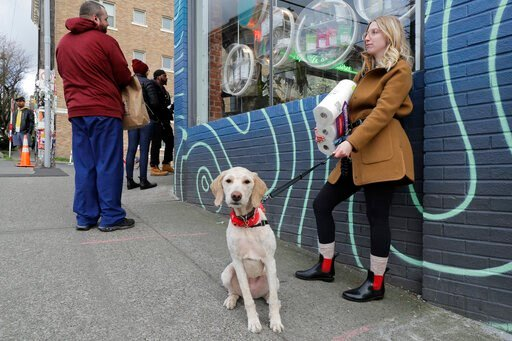 (AP Photo/Ted S. Warren). In this photo taken March 24, 2020, Mia Grace, right, holds a package of toilet paper as she and her dog Breezy observe social distancing chalk marks on the sidewalk while waiting to get in to The Reef Capitol Hill, a marijuan...