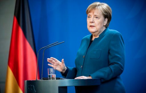 (Michael Kappeler/Pool photo via AP). German Chancellor Angela Merkel speaks at a press conference about coronavirus, in Berlin, Sunday, March 22, 2020. German authorities have issued a ban on more than two people meeting outside of their homes, which ...