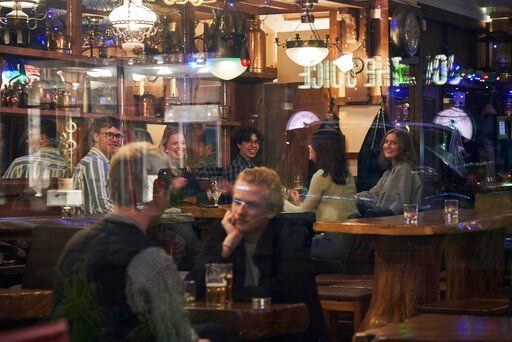 (AP Photo/David Keyton). People sit in a bar in Stockholm, Wednesday, March 25, 2020. The streets of Sweden's capital are quiet but not deserted. Sweden has some of the most relaxed measures in Europe in the fight against the coronavirus outbreak. So f...
