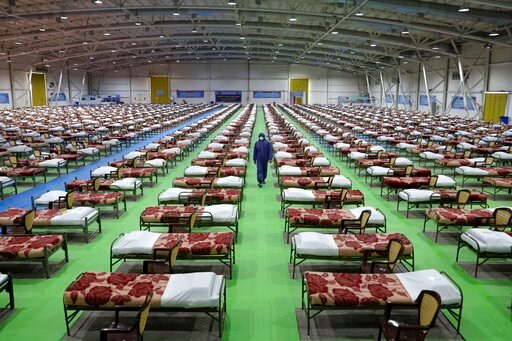 (AP Photo/Ebrahim Noroozi). A member of the Iranian army walks past rows of beds at a temporary 2,000-bed hospital for COVID-19 coronavirus patients set up by the army at the international exhibition center in northern Tehran, Iran, on Thursday, March ...