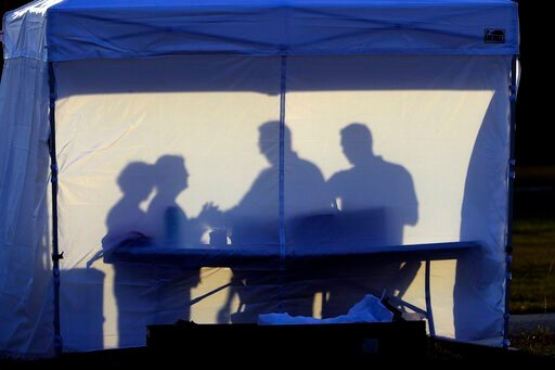 (AP Photo/Chris O'Meara). FILE - In this Wednesday, March 25, 2020 file photo, medical personnel are silhouetted against the back of a tent before the start of coronavirus testing in the parking lot outside of Raymond James Stadium in Tampa, Fla. As ca...