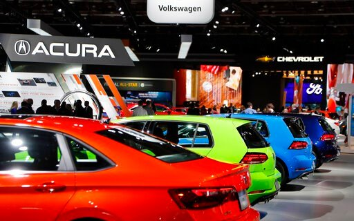 (AP Photo/Carlos Osorio, File). FILE - In a Jan. 15, 2019 file photo, signage for automakers Volkswagen, Acura, Chevrolet and Ford, at the North American International Auto Show in Detroit. The North American International Auto Show said that it will c...