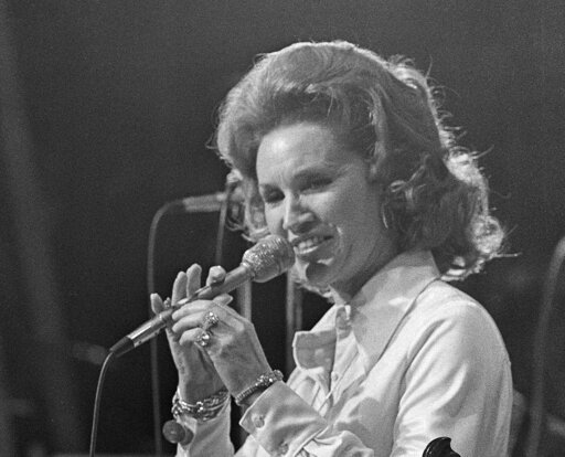 "(AP Photo/John Duricka, File). FILE - In a March 18, 1974 file photo, Country music star Jan Howard performs during the Grand Ole Opry's last show at Ryman Auditorium in Nashville, Tenn.Howard, who had a No. 1 country hit ""For Loving You"" with Bill And..."