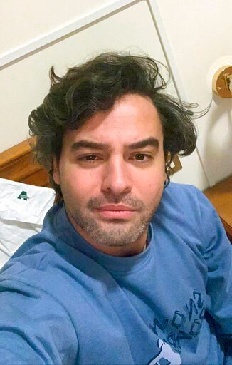(Andrea Napoli via AP). Andrea Napoli, 33, takes a selfie in a hotel being used for patients recovering from coronavirus, in Rome, Sunday, March 29, 2020. Andrea Napoli, a lawyer in Rome, developed a cough and fever less than a week after Italy's premi...
