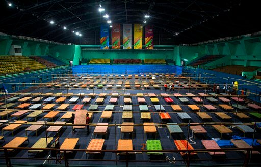 (AP Photo/Anupam Nath). Indian workers arrange beds to prepare a quarantine center at the Sarusojai sports complex in Gauhati, India, Saturday, March 28, 2020. The new coronavirus causes mild or moderate symptoms for most people, but for some, especial...
