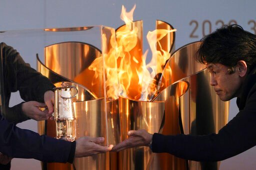 (AP Photo/Eugene Hoshiko, File). FILE - In this March 25, 2020, file, photo, officials light a lantern from the Olympic Flame at the end of a flame display ceremony in Iwaki, northern Japan. Before the Olympics were postponed, Japan looked like it had ...