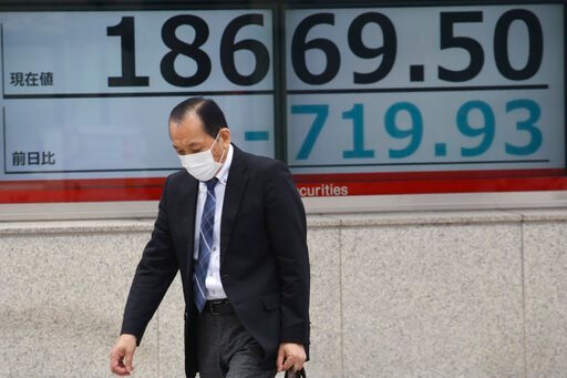 (AP Photo/Koji Sasahara). A man walks by an electronic stock board of a securities firm in Tokyo, Monday, March 30, 2020. Asian shares started the week with further losses as countries reported surging numbers of infections from the coronavirus that ha...