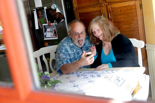 (AP Photo/Matt York). Seen through their kitchen window, Allan and Debbie Cameron contact their grandchildren via the internet Wednesday, March 25, 2020, in Chandler, Ariz. Debbie, 68, has asthma which makes her one of the people most at risk from the ...