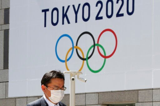 (AP Photo/Koji Sasahara, File). FILE - In this Wednesday, March 25, 2020, file photo, a man walks in front of a Tokyo Olympics logo at the Tokyo metropolitan government headquarters. The postponement of the Tokyo Games has catapulted the sports organiz...
