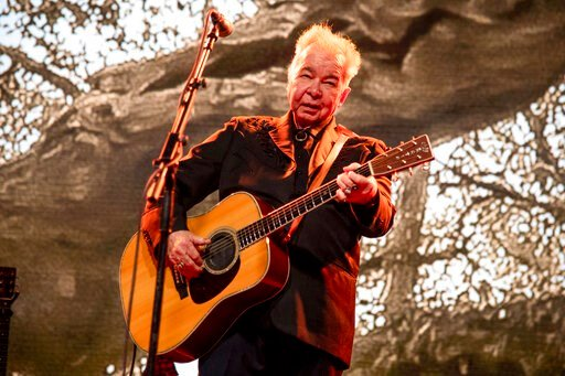 (Photo by Amy Harris/Invision/AP, File). FILE - This June 15, 2019 file photo shows John Prine performing at the Bonnaroo Music and Arts Festival in Manchester, Tenn. The family of John Prine says the singer-songwriter is critically ill and has been pl...