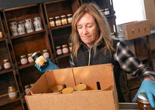 (Dave Zajac/Record-Journal via AP). Linda DeFrancesco stocks shelves with her farm's own salsa, spreads, veggies and salsa at DeFrancesco Farm Stand in Northford, Conn., Thursday, March 26, 2020. Businesses across the state are worried about the impact...