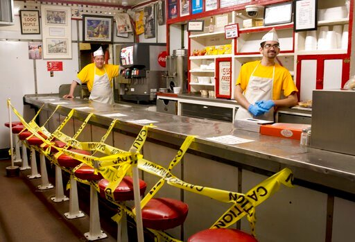 (Heather Rousseau/The Roanoke Times via AP). Texas Tavern employees Chris Dobe, left, and Nick Moore wait for take out orders on Monday night, March 30, 2020. Though customers are tipping well, and the diner is still open 24-7, Moore said they are maki...