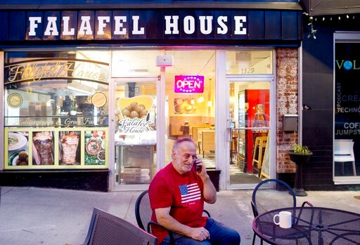 (Heather Rousseau/The Roanoke Times via AP). Clade Karim takes a take out order over the phone for Falafel House in downtown Grandin on Monday night, March 30, 2020. Karim is friends with the owner and is a self proclaimed volunteer helper for the rest...