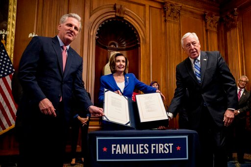 (AP Photo/Andrew Harnik). House Speaker Nancy Pelosi of Calif., House Minority Leader Kevin McCarthy of Calif., left, and House Majority Leader Steny Hoyer of Md., right, holds up the Coronavirus Aid, Relief, and Economic Security (CARES) Act after Pel...