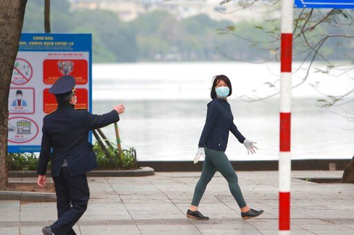 (AP Photo/Hau Dinh). A security officer talks to a woman walking on a street in Hanoi, Vietnam, Wednesday, April 1, 2020. Vietnam on Wednesday starts two weeks of social distancing to contain the spread of COVID-19. The new coronavirus causes mild or m...