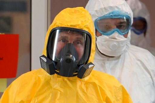 (Alexei Druzhinin, Sputnik, Kremlin Pool Photo via AP, File). FILE - In this file photo taken on Tuesday, March 24, 2020, Russian President Vladimir Putin wearing a protective suit enters a hall during his visit to the hospital for coronavirus patients...