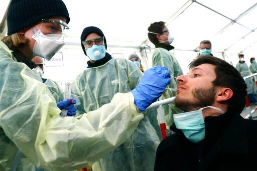 (AP Photo/Matthias Schrader, File). FILE - In this March 23, 2020, file photo, medical employees demonstrate testing, at a coronavirus test center for public service employees, during a media presentation in Munich, Germany. Labs were quick to ramp up ...