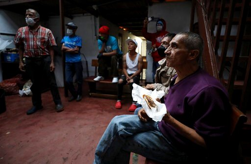 "(AP Photo/Fernando Vergara). An elderly man eats a hamburger that was donated by Emiliano Moscoso in a boarding house in Bogota, Colombia, Monday, March 30, 2020. Moscoso recently launched a program called ""Solidarity Menu"" to feed people in need durin..."
