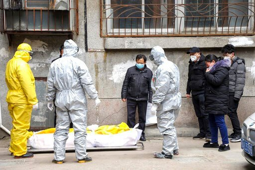 (Chinatopix via AP, File). FILE - In this Feb. 1, 2020, file photo, funeral home workers remove the body of a person suspected to have died from the coronavirus outbreak from a residential building in Wuhan in central China's Hubei Province. Skepticism...