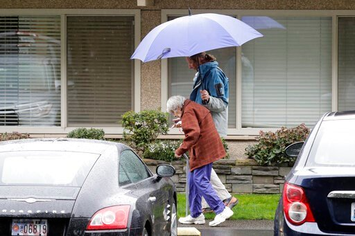 (AP Photo/Ted S. Warren). In this March 6, 2020 photo, Charlie Campbell, right, walks with his mother, Dorothy Campbell, to visit his father, Gene, who was staying at the time at the Life Care Center in Kirkland, Wash. Charlie Campbell is nearly 13 yea...
