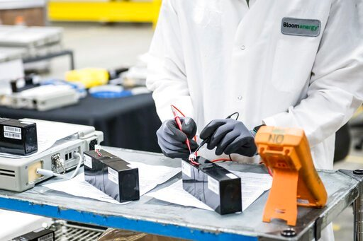 (Beth LaBerge/KQED via AP, Pool, File). FILE - In this March 28, 2020, file photo, David Yee, an NPI mechanical engineer, tests voltage of new batteries at Bloom Energy in Sunnyvale, Calif. The COVID-19 outbreak has prompted companies large and small t...