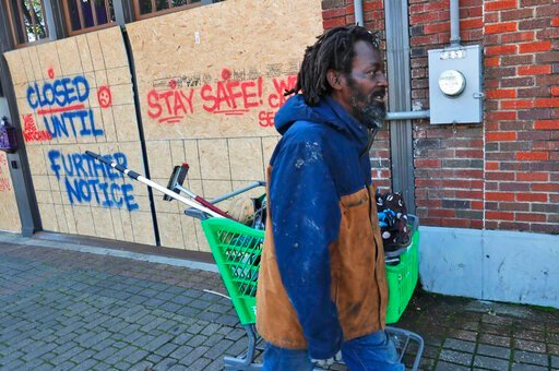 (AP Photo/LM Otero). FILE - In this Tuesday, March 31, 2020 file photo, Vincent Amos, who identified himself as homeless, pulls a shopping cart with his belongings amid businesses closed by concerns of the COVID-19 coronavirus in the Deep Ellum section...