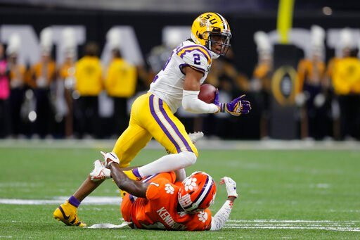 (AP Photo/Gerald Herbert). LSU wide receiver Justin Jefferson runs over Clemson cornerback Derion Kendrick during the first half of a NCAA College Football Playoff national championship game Monday, Jan. 13, 2020, in New Orleans.