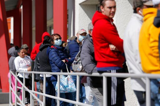 (AP Photo/John Locher). FILE - In this March 17, 2020 file photo, people wait in line for help with unemployment benefits at the One-Stop Career Center in Las Vegas. About half of all working Americans say they or a member of their household have lost ...