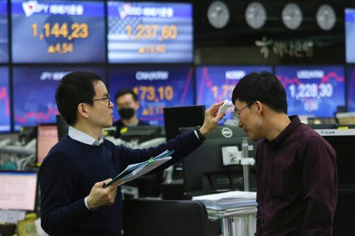 (AP Photo/Ahn Young-joon). A currency trader checks the temperature of his colleague at the foreign exchange dealing room of the KEB Hana Bank headquarters in Seoul, South Korea, Friday, April 3, 2020. Asian stocks were mixed Friday after Wall Street g...