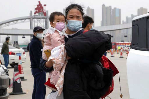 (AP Photo/Ng Han Guan). In this Thursday, April 2, 2020, photo, a woman holding a child walks away from the expressway gate at the border of Wuhan city in central China's Hubei province. Millions of Chinese workers are streaming back to factories, shop...