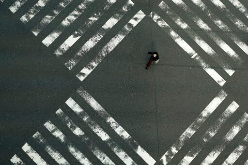 (AP Photo/Eugene Hoshiko). A woman walks through an empty pedestrian crossing in the Ginza shopping district Friday, April 3, 2020, in Tokyo. The new coronavirus causes mild or moderate symptoms for most people, but for some, especially older adults an...