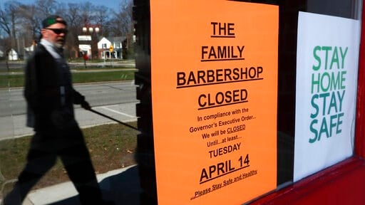 (AP Photo/Paul Sancya). A pedestrian walks by The Family Barbershop, closed due to a Gov. Gretchen Whitmer executive order, in Grosse Pointe Woods, Mich., Thursday, April 2, 2020. The coronavirus COVID-19 outbreak has triggered a stunning collapse in t...