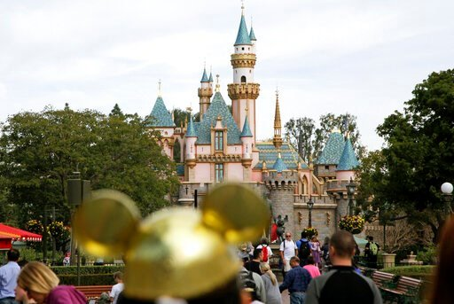 (AP Photo/Jae C. Hong, File). FILE - In this Jan. 22, 2015, file photo, visitors walk toward Sleeping Beauty's Castle in the background at Disneyland Resort in Anaheim, Calif.  Saying they don't know when they'll be able to re-open many of their busine...