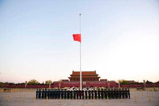 (Ju Huanzong/Xinhua via AP). In this photo released by China's Xinhua News Agency, an honor guard stands in formation as a Chinese national flag flies at half-staff at Tiananmen Square in Beijing, Saturday, April 4, 2020. China plans to pause for 3 min...