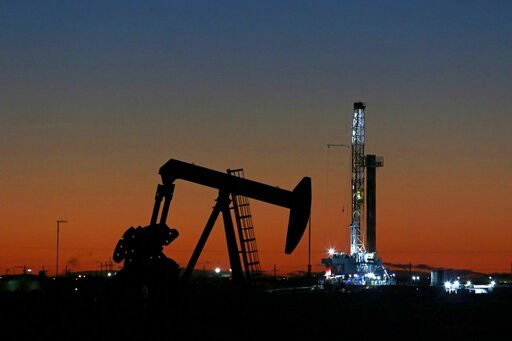 (Jacob Ford/Odessa American via AP, File, File). FILE- This Oct. 9, 2018, file photo shows an oil rig and pump jack in Midland, Texas.  Goldman Sachs is warning of another sharp drop in oil prices, Thursday, March 26, 2020, saying some oil producers ar...