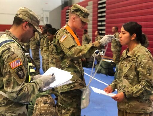 (U.S. Army via AP). In this image provided by the U.S. Army, recent Army basic combat training graduates have their temperatures taken as they arrive at Fort Lee, Va, on March 31, 2020, after being transported using sterilized buses from Fort Jackson, ...